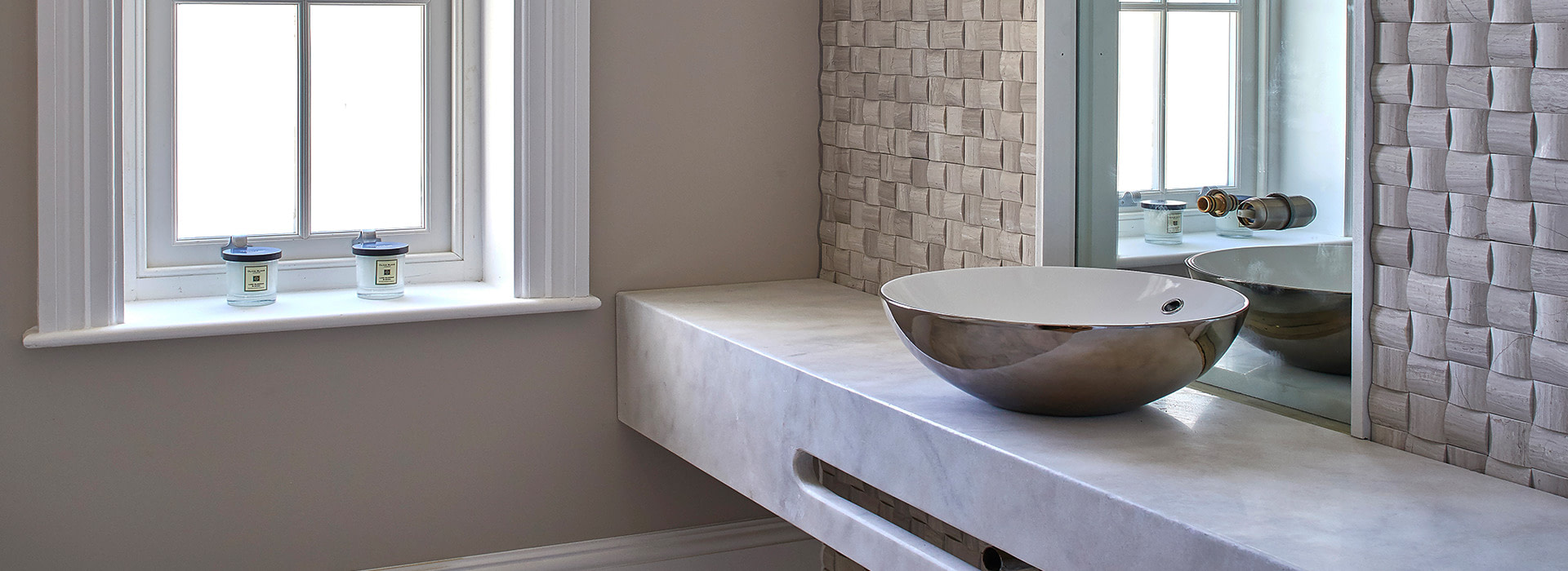 Marble vanity with textured bathroom wall tiles